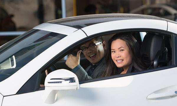 Happy car buyers in a fresh used car.